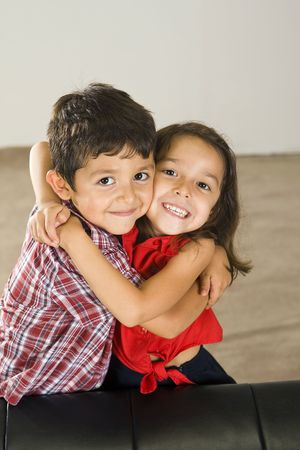 Cute brother and sister sitting on a couch Banque d'images