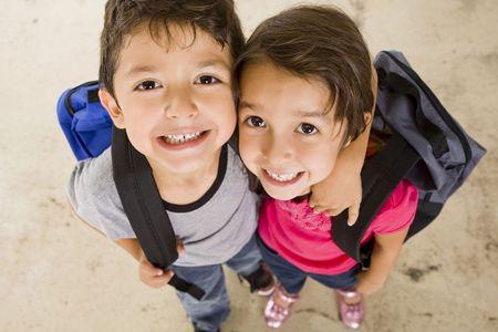 school backpack: Niño y niña con sus bolsas de libros Foto de archivo