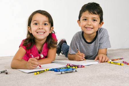 Little boy and girl laying on the carpet coloring Stock Photo