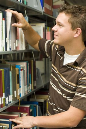 Man looking at books in a library photo