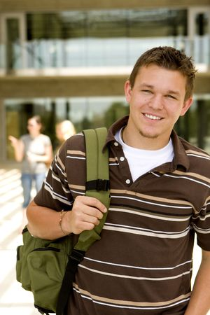 Young man at school holding a book bag photo