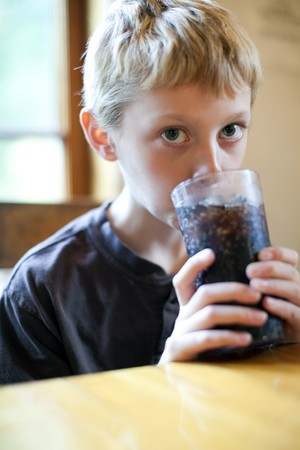 Little boy drinking a glass of soda Stock Photo