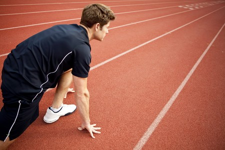 Man ready to start running on a track photo
