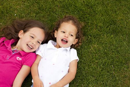 Cute little sisters laying in grass photo