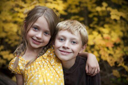 兄と妹の外に座っています。 写真素材