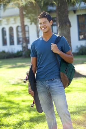 Student with Skateboard und Rucksack außerhalb der Schule