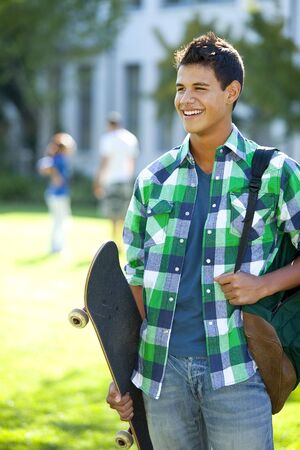 Student with skateboard and backpack outside school photo