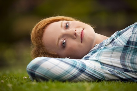 Young woman relaxing outside in the grass