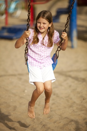 Little girl playing at a park swinging photo