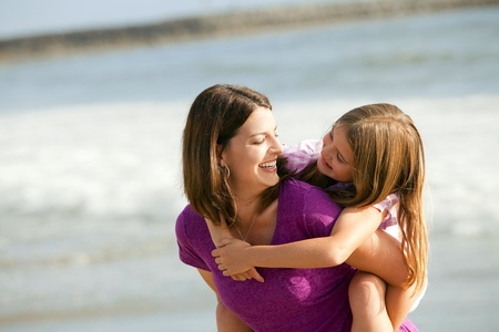 Loving mother and daughter playing on the beach  photo