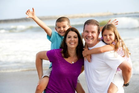 Happy loving family playing on the beach photo