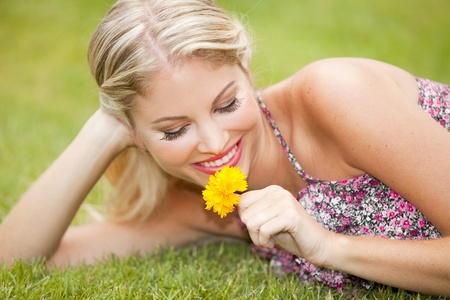 Beautiful youn woman sitting in the grass with a yellow flower photo
