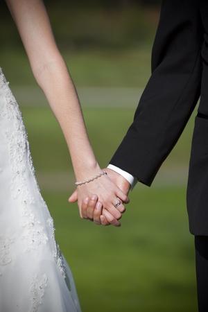 Primer plano de la novia y el novio tomados de la mano