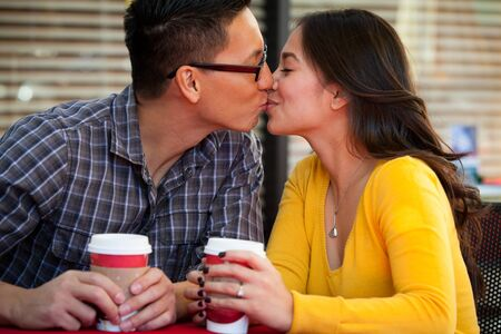 Happy young couple drinking coffee outside cafe photo