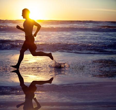 Man lopen op het strand bij zonsondergang Stockfoto
