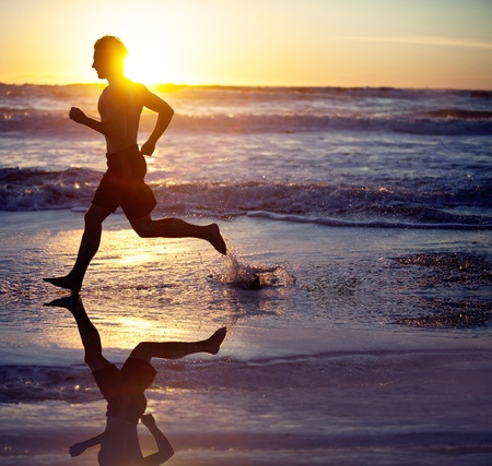 man in air: Man running on the beach at sunset