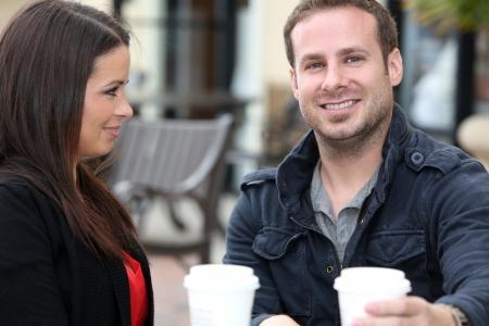 젊은 부부는 밖에서 커피를 마시는