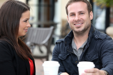 Young couple drinking coffee outside