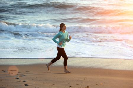 Woman running on the beach photo