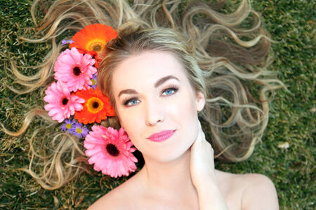 Attractive woman lying in the grass with flowers around hair