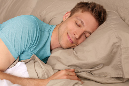 Young man peacefully sleeping in bed