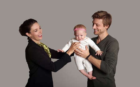 Business woman and mother handing child to stay at home father  Stock Photo