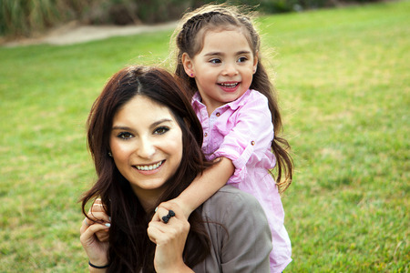 diverse family: Diverse mom and daughter sitting in the grass