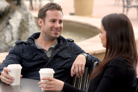 Young couple drinking coffee outside photo