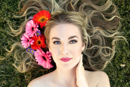 Attractive woman lying in the grass with flowers around hair photo