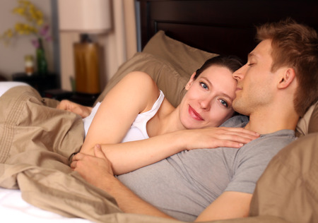 Happy young couple laying in bed photo