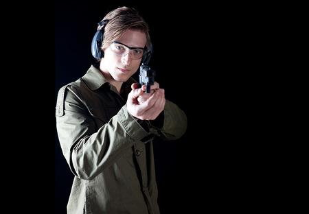 Man aiming a hand gun wearing protective gear