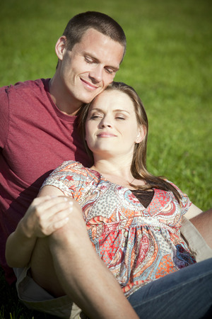 Loving couple sitting in the grass photo