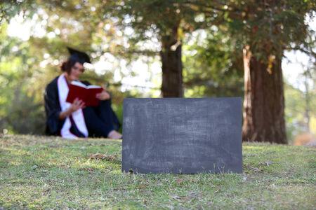 18's: Graduate sitting behind blank chalkboard - room for copy
