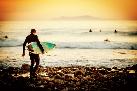 surfboard: Surfer on the beach at sunset Stock Photo