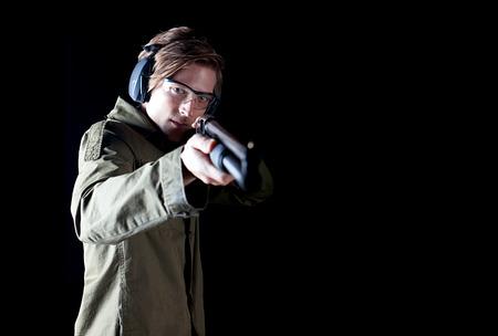 Man aiming a shotgun wearing protective gear photo