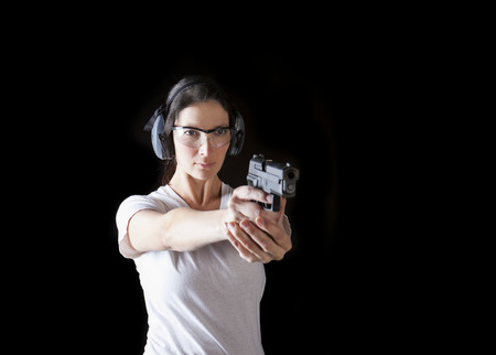 Woman holding a gun with protective gear Stock Photo
