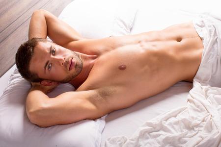 deitado: Atraente jovem deitado na cama Imagens