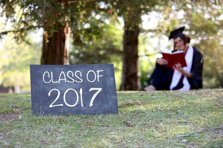room for copy: Graduate sitting behind blank chalkboard - room for copy
