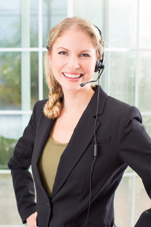 head set: Business woman talking on a head set in her office