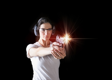 protective: Woman firing a gun with protective gear Stock Photo