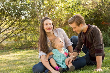 family outside: Happy young family sitting in the grass outside Stock Photo