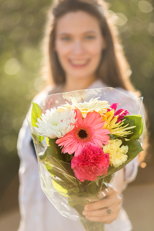 flower bunch: Beautiful woman holding out a bouquet of flowers outside Stock Photo