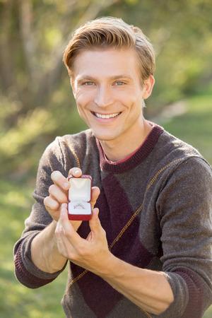 man kneeling: Man kneeling outside proposing with diamond ring