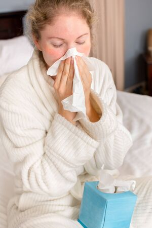 flu: Young sick woman holding tissue sitting  in bed Stock Photo
