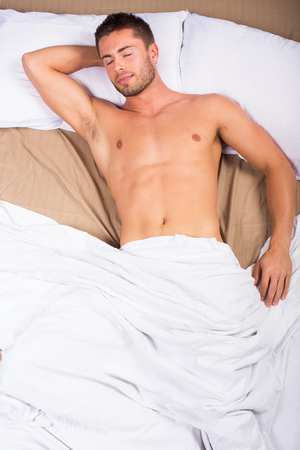 wellness sleepy: Birdseye view of an attractive man laying in bed
