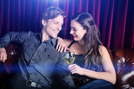 Young flirty couple with wine at a club lounge Imagens