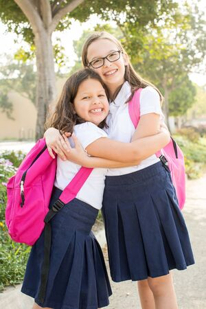bookbag: Two little girls with backpacks on their way to school