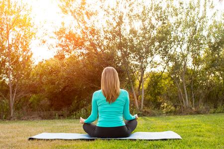yoga outside: Woman doing yoga poses outside in a park