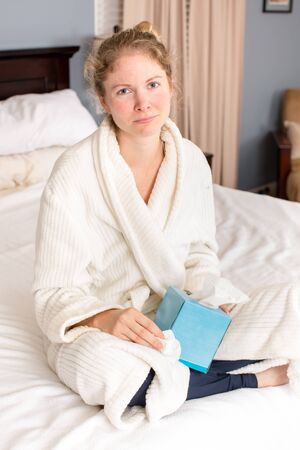 house robe: Young sick woman holding tissue sitting  in bed Stock Photo