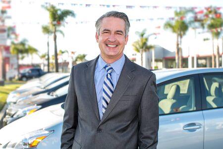 car retailer: Car salesman standing outside a dealership